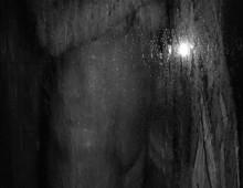 une femme nue derrière une vitre de douche