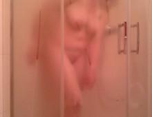 Une femme ronde nue derrière la vitre de la douche